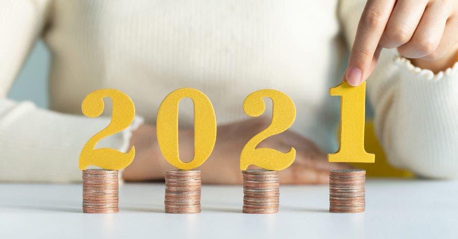 Personas poniendo número 2021 en monedas