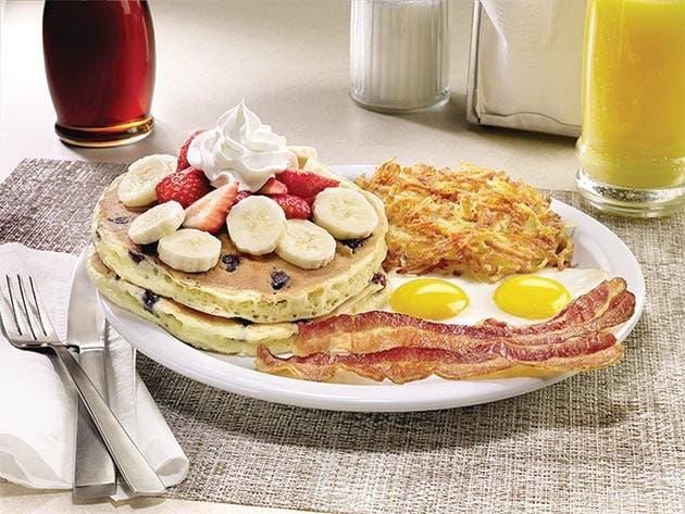 un plato de pancakes con huevos, has brown y tocino