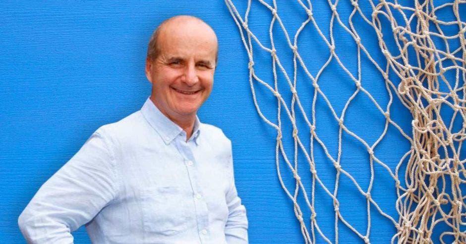 un hombre calvo sonriendo sobre un fondo azul y una red de arrastre