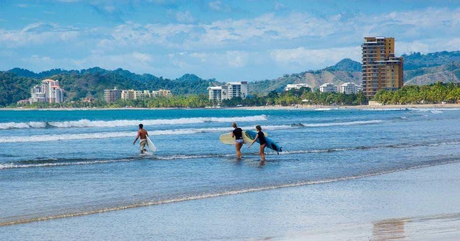 Jóvenes surfeando en playa Jacó de Garabito