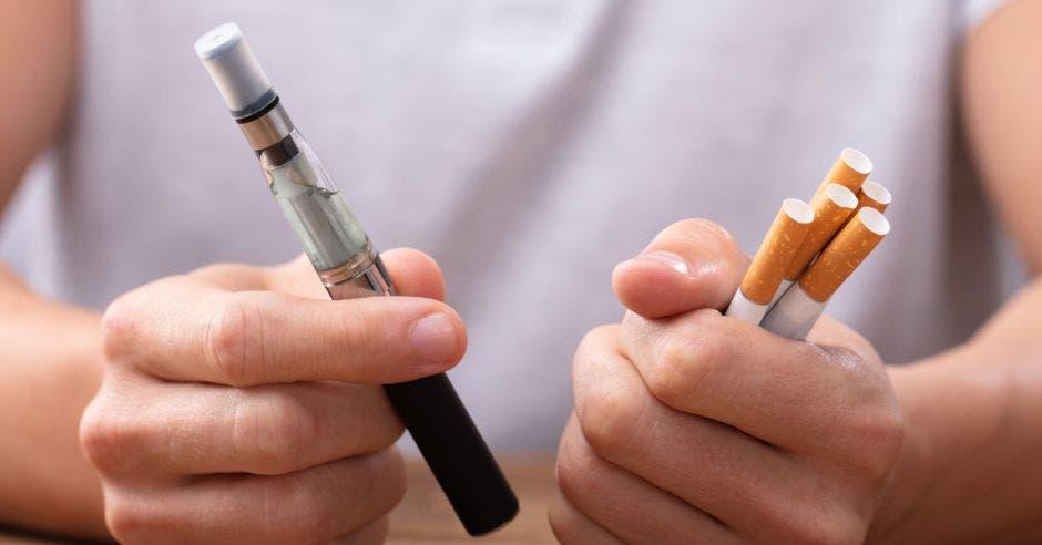 una mano sosteniendo un vaporizador y otra mano sosteniendo cigarros
