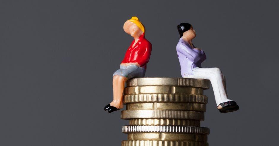 Dos personas sentadas sobre una torre de monedas