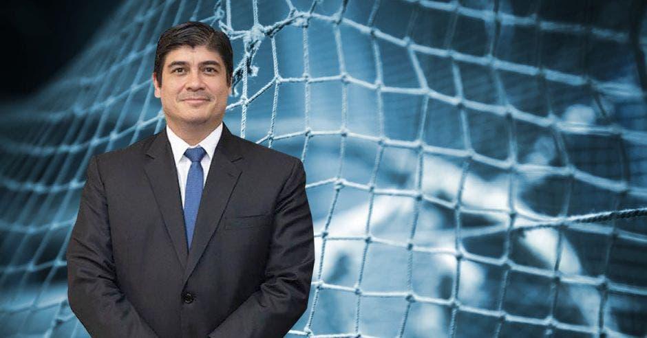 un hombre de traje y corbata azul posa sobre una red de arrastre