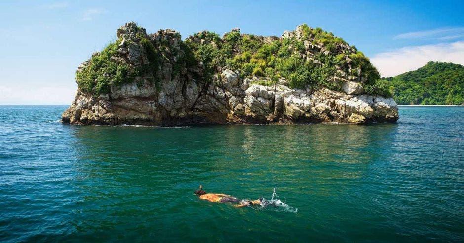 un hombre hace esnórquel cerca de una isla