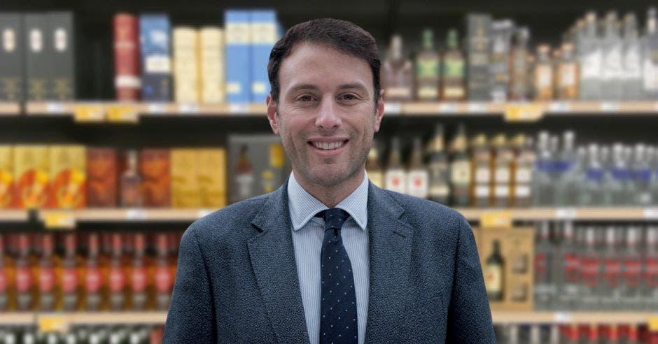 Un hombre con saco y corbata sobre un estante de licores