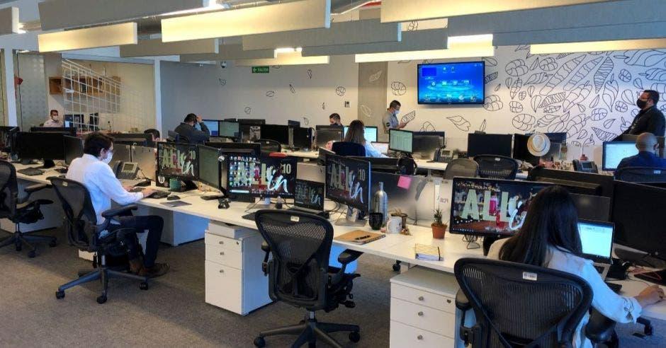 Un grupo de personas sentadas en una oficina haciendo labores en una computadora
