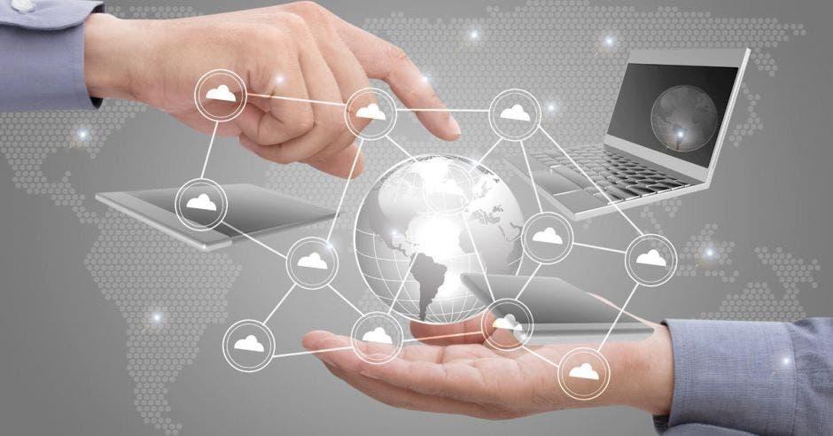 Unas manos sosteniendo un mundo y una computadora atrás