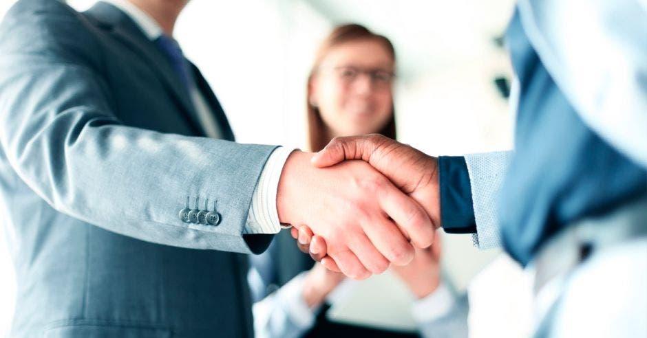Dos hombres estrechando las manos y mujer detrás en segundo plano