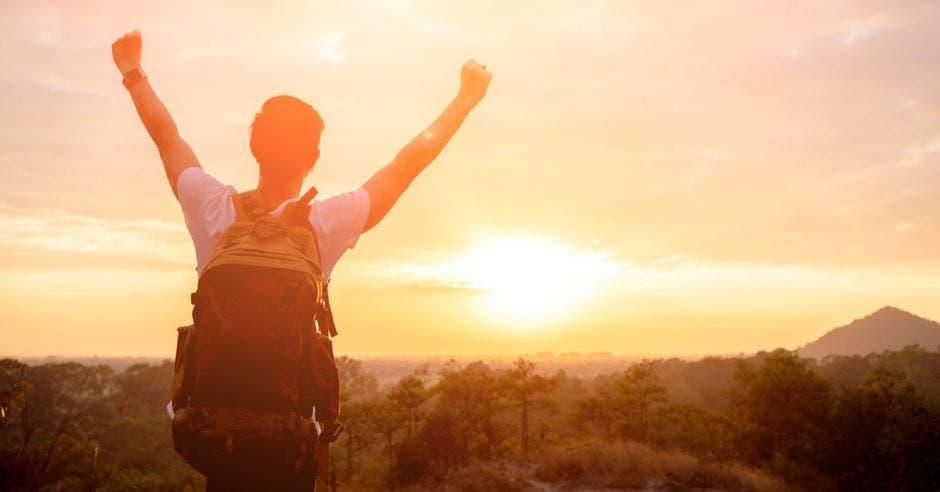 Un hombre con las manos levantadas hacia el sol