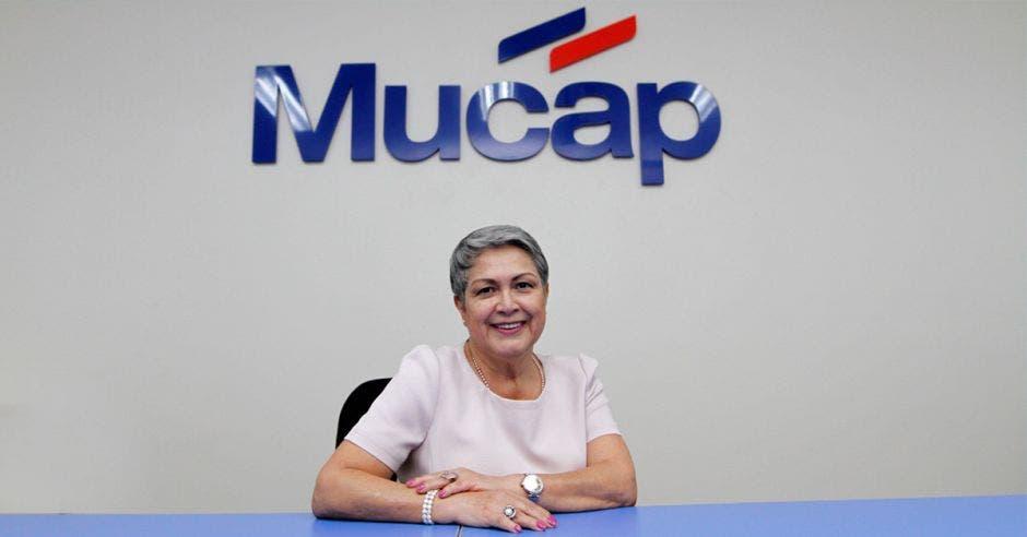 Mujer sentada con logo de Mucap de fondo