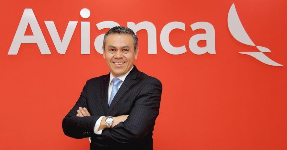 un hombre de traje y corbata sonríe sobre un fondo que dice Avianca en letras blancas y fondo rojo