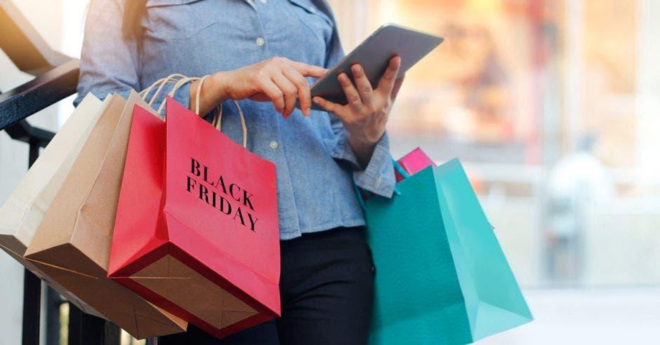 Una mujer con varias bolsas de compra revisando su tablet