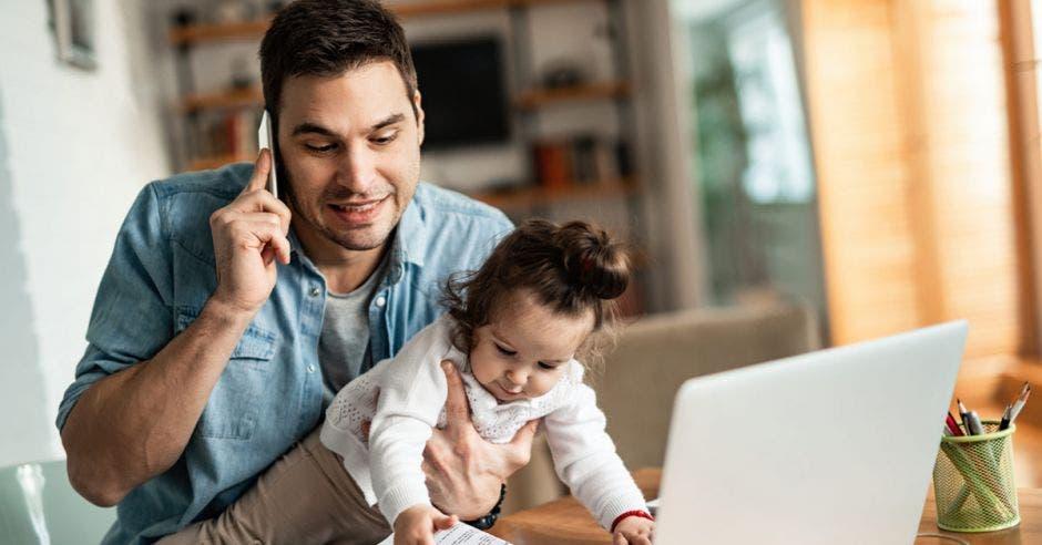 Un padre de familia sosteniendo a una bebé mientras hace teletrabajo