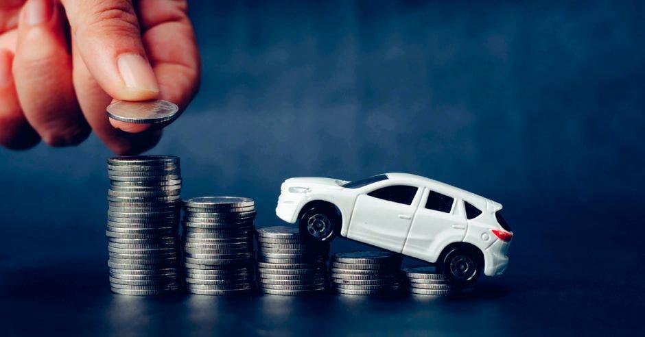 Carro de juguete subiendo en columnas con monedas