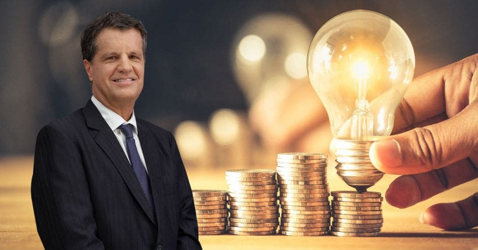 Hombre frente a bombillo y monedas