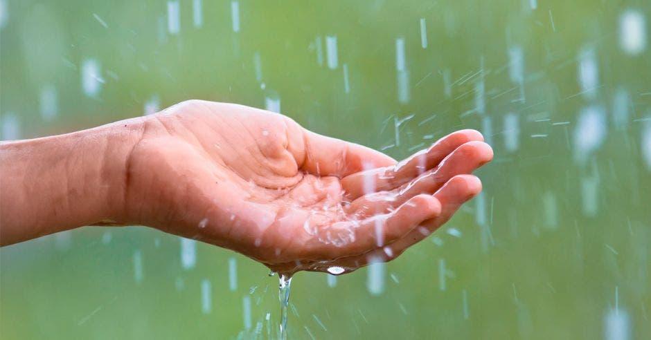 una mano recogiendo agua de lluvia