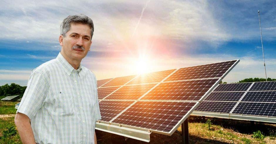 un hombre de bigote y camisa blanca posa sobre un fondo de paneles solares