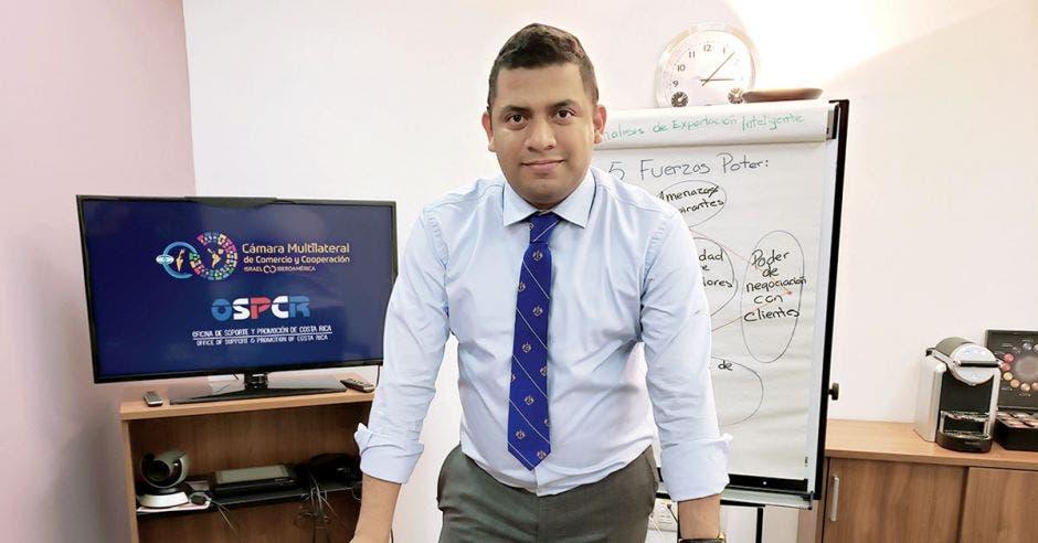 un hombre de camisa celeste y corbata azul de pie en una oficina
