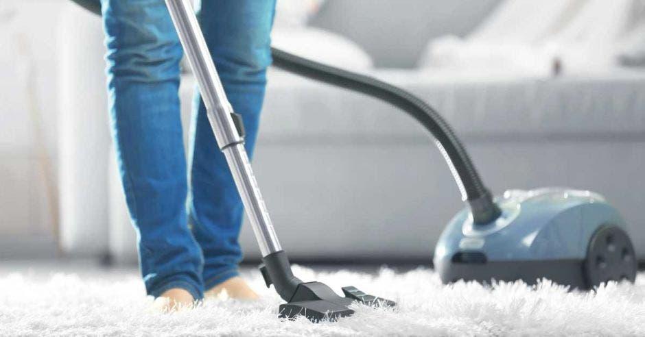 Una mujer limpiando una alfombra