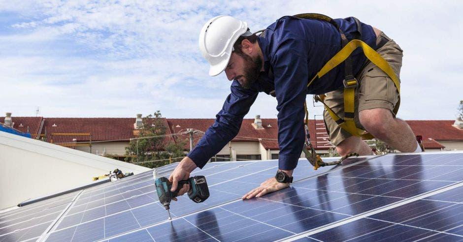 un hombre instala un panel solar en el techo de una casa