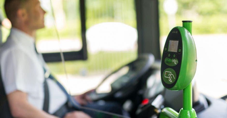 conductor de autobus de fondo y dispostivo de pago electrónico en primer plano