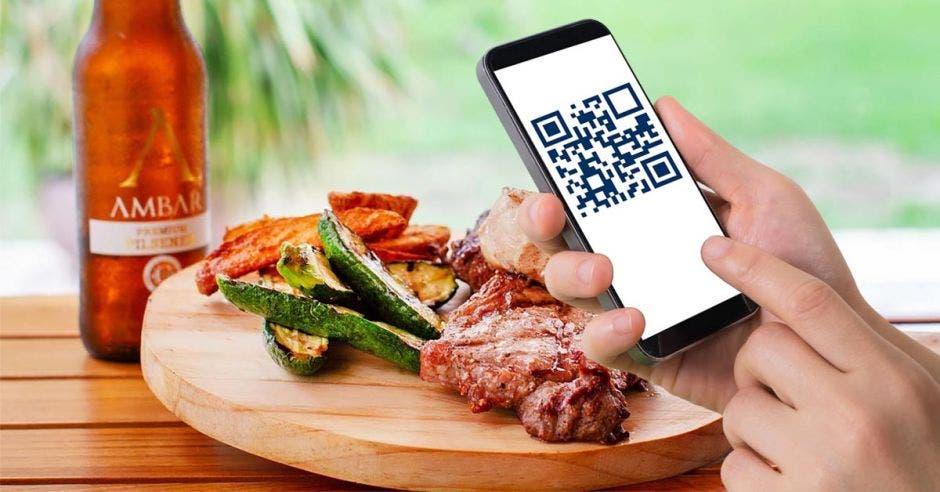 Una persona escanea con código QR el menú de un restaurante