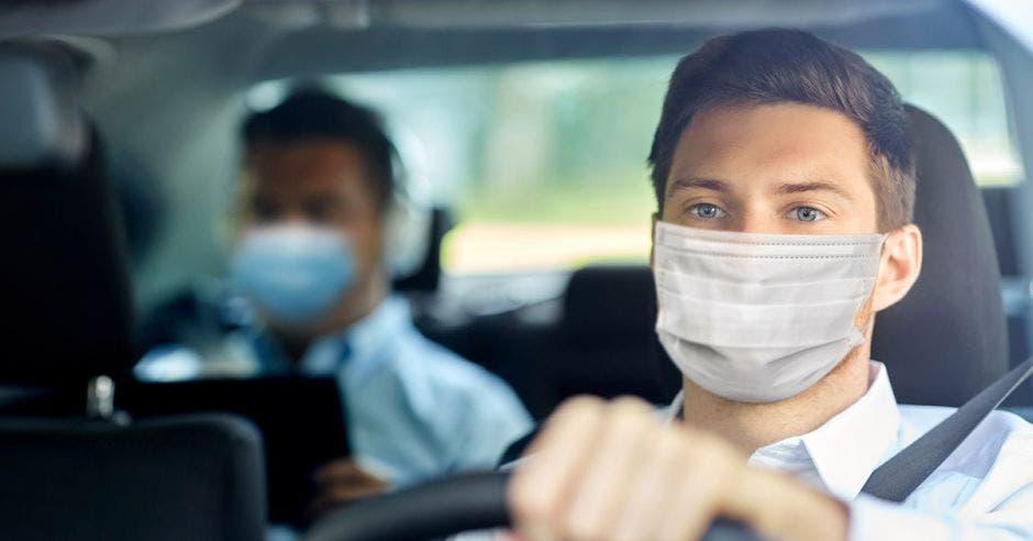 un hombre con mascarilla conduce un vehículo