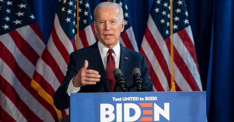 un hombre da un discurso sobre un atril. Tiene detrás cuatro banderas de los Estados Unidos