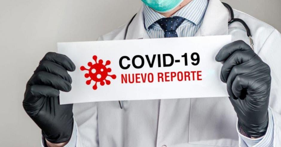 Hombre con guantes sostiene reporte de casos Covid-19