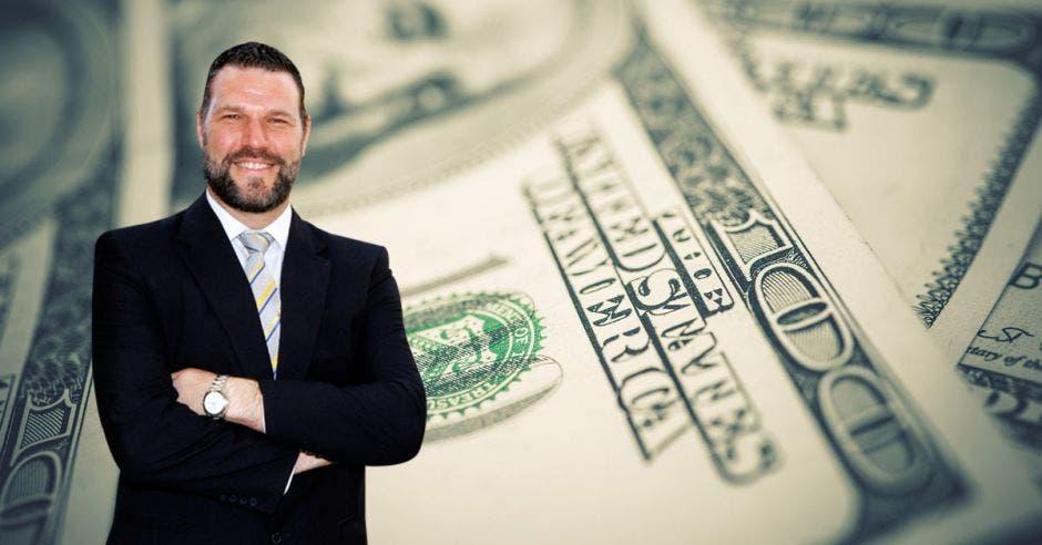 Hombre de traje con brazos cruzados frente a dólares