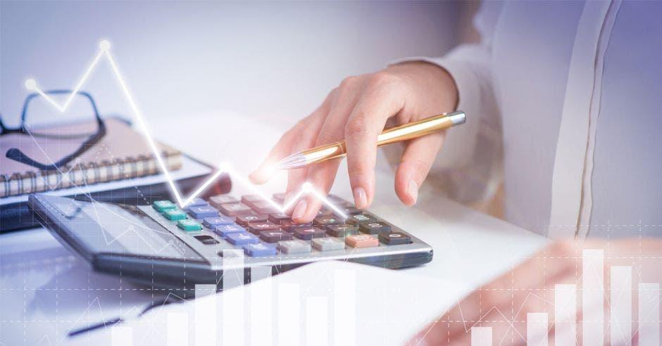 Mano de mujer digita en calculadora