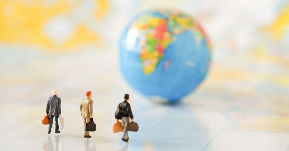 tres hombres con un maletín ejecutivo caminan hacia un globo terráqueo
