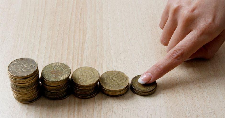 Dedo colocado en una columna de monedas