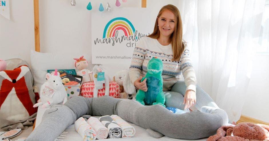 Un mujer de pelo castaño posa sobre una cama llena de juguetes para infantes