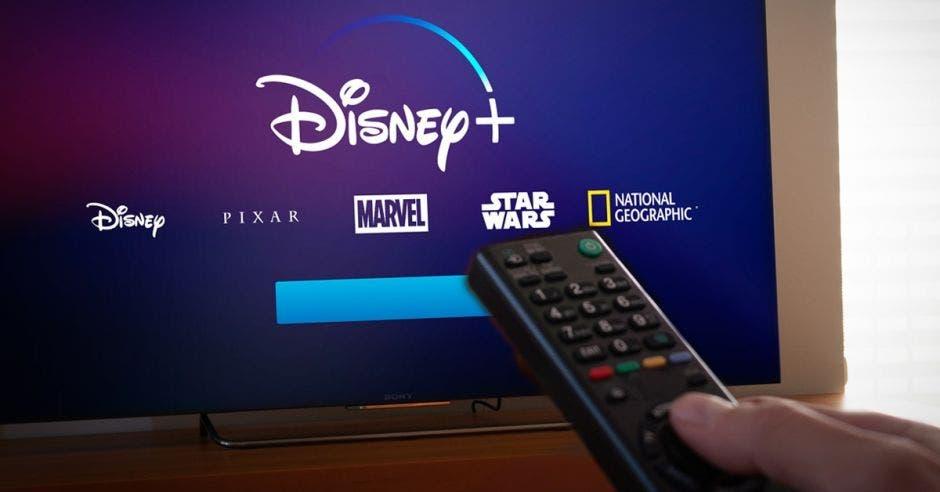 Disney+ en televisor y persona con control remoto