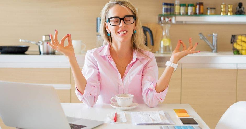 Mujer con camisa rosa y lentes negros, sentada con manos levantadas tocando pulgar con dedo índice