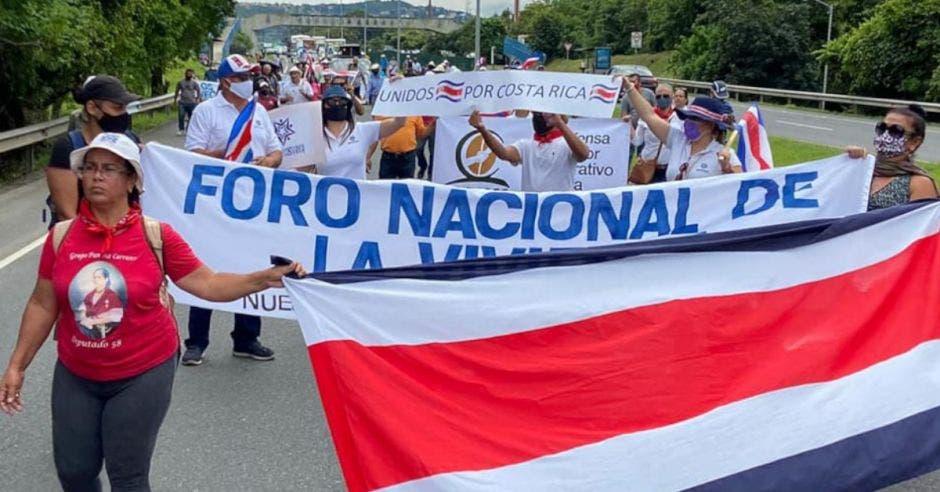 una serie de personas desfila con una bandera de Costa Rica