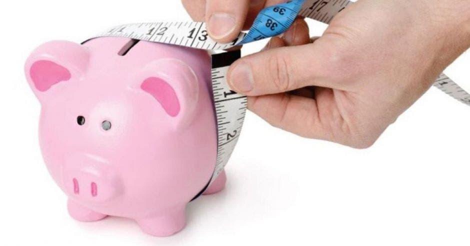 Alcancía de cerdo y persona poniendo cinta métrica