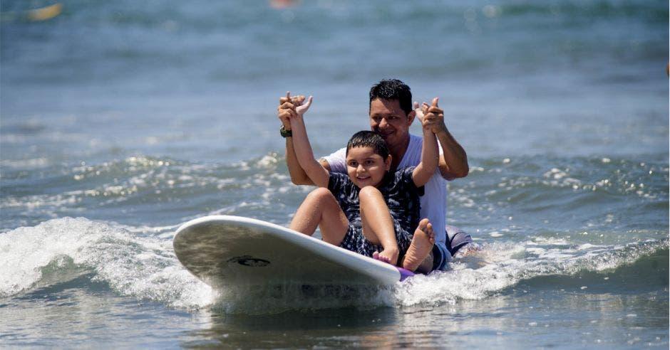 un padre con su hijo en una tabla de surf