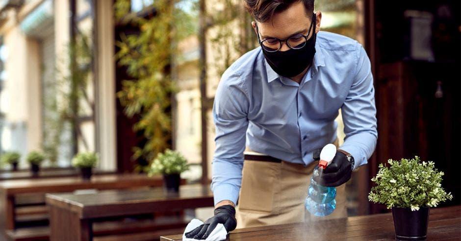 un hombre limpia una mesa con líquido desinfectante