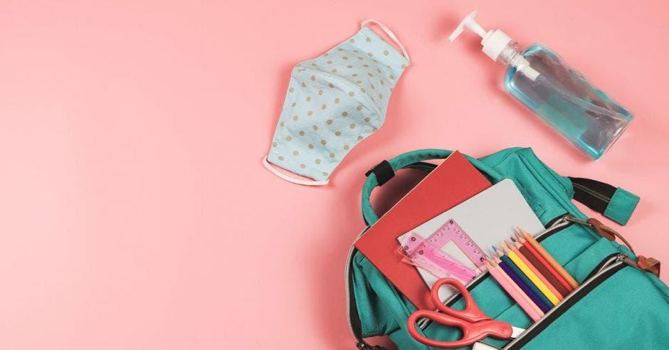 mochila con artículos escolares sobre fondo rosa, al lado de un cubrebocas y gel antibacterial