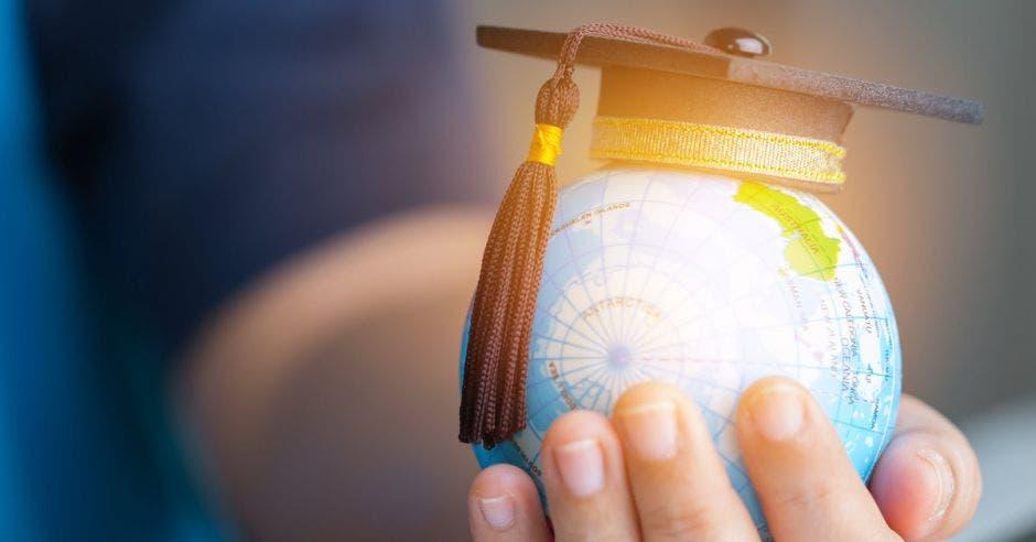 Un globo terráqueo con un birrete de graduación encima, sobre una mano