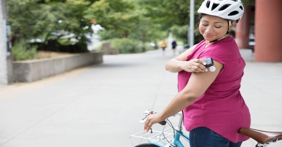 Una mujer tocando su sensor de Abbott mientras anda en bicicleta