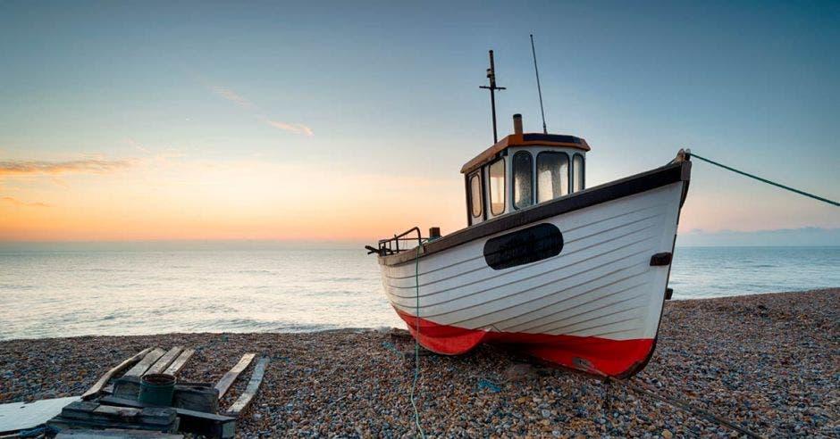 un barco pesquero color blanco con rojo, encallado en una playa