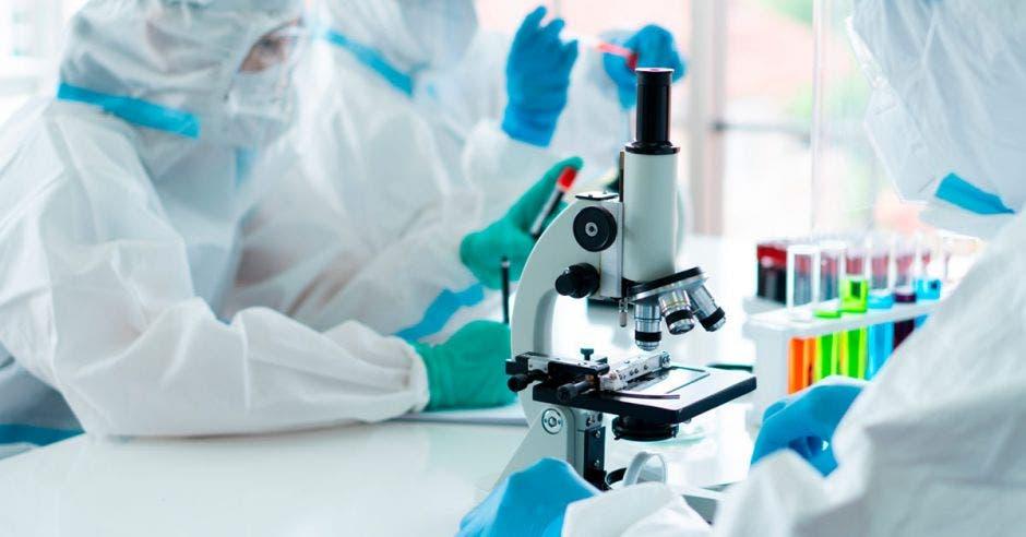 Personas en laboratorio viendo con microescopio