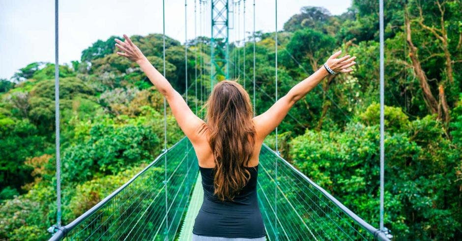 Una mujer con los brazos abiertos al cielo sobre un puente verde