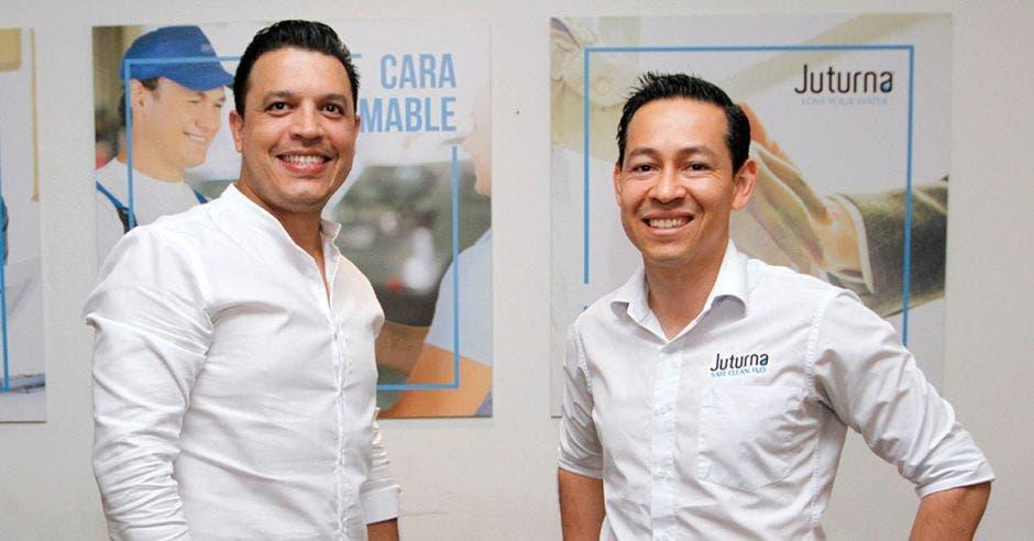 un hombre alto de camisa blanca junto a otro hombre de menor estatura, también con camisa blanca
