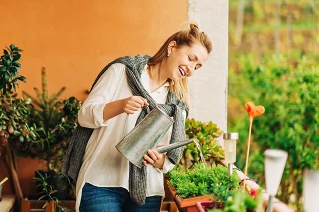 Una muchacha cuida las plantas de su hogar