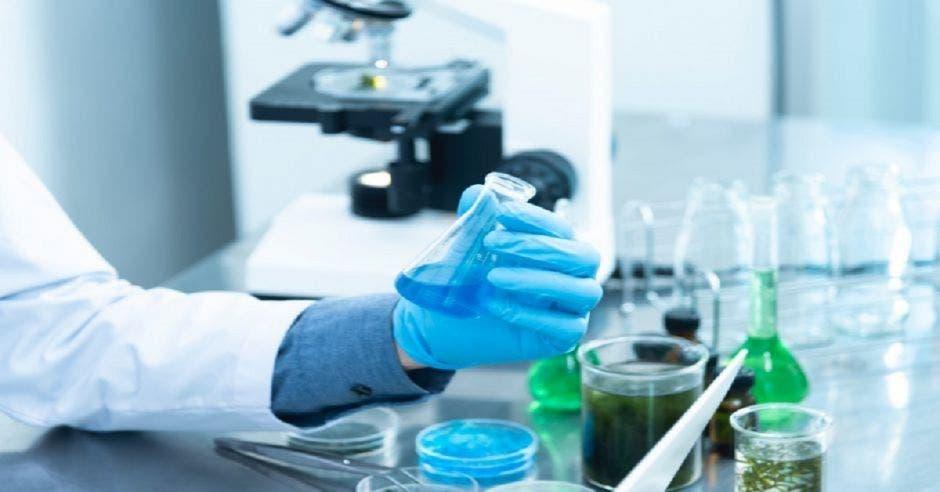 Una mano sosteniendo una fórmula química en un laboratorio