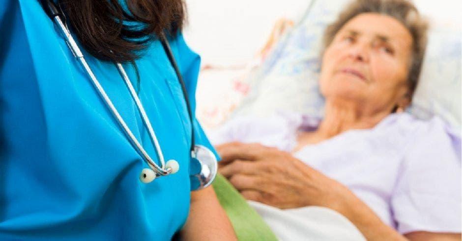 Una adulta mayor en una cama de hospital y una profesional de la salud a su lado